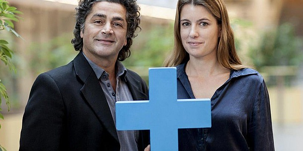 Two people behind a blue cross