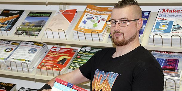 Mann steht vor einem Regal mit Zeitschriften und hält Bücher in der Hand