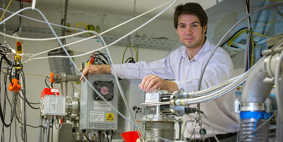Andreas Hauser steht rechts im Bild. Rund um ihn herum ist Laborequipment zu sehen.