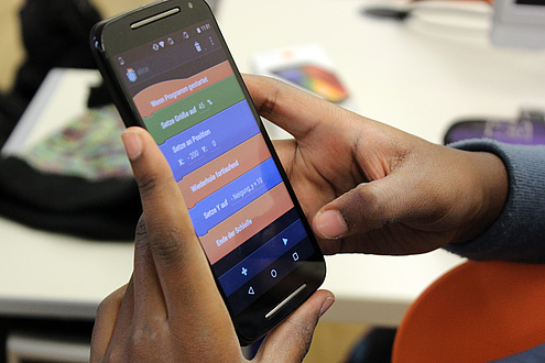 Ein Kind im Unterstufenalter hält ein Smartphone in Händen und programmiert