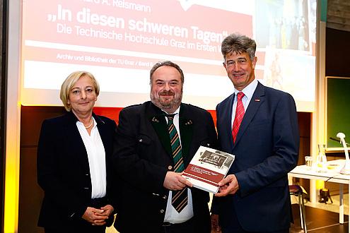 Die Leiterin des Verlages der TU Graz, Ulrike Krießmann, Autor und TU Graz-Archivar Bernhard A. Reismann sowie TU Graz-Rektor Harald Kainz stehen nebeneinander. Die Herren halten gemeinsam eine Ausgabe des Buches in Händen.