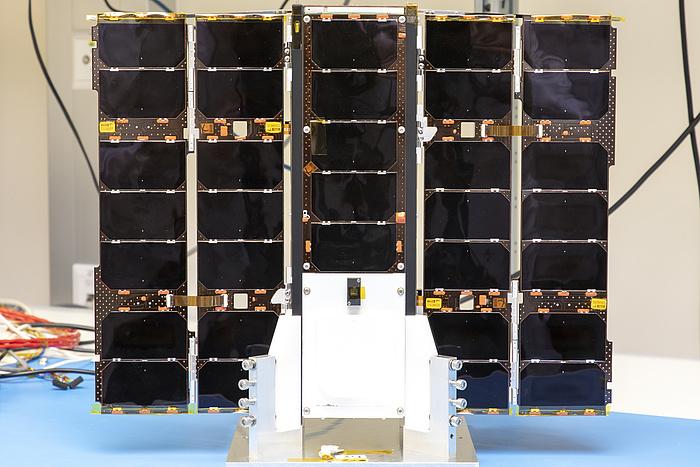 Der Satellit steht auf einem Tisch. Seine schwarzen Solarpanele zeigen nach vorne.