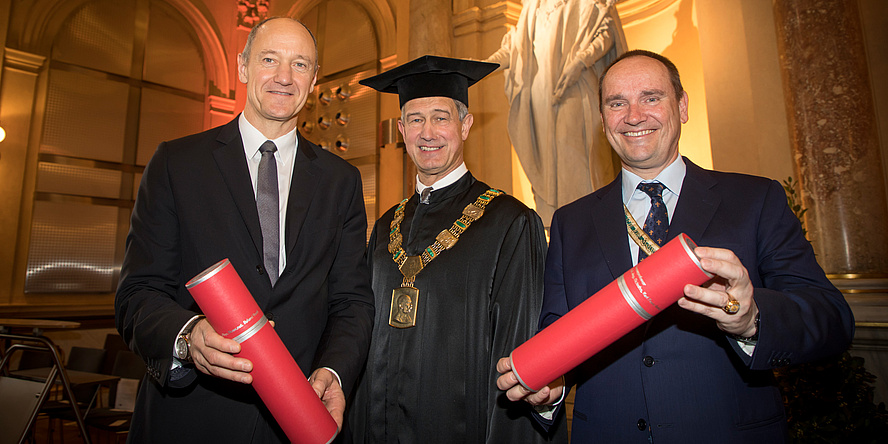 Rektor Kainz im schwarzen Talar, neben ihm Roland Busch und Robert Fischer, die jeweils eine rote Rolle in Händen halten.