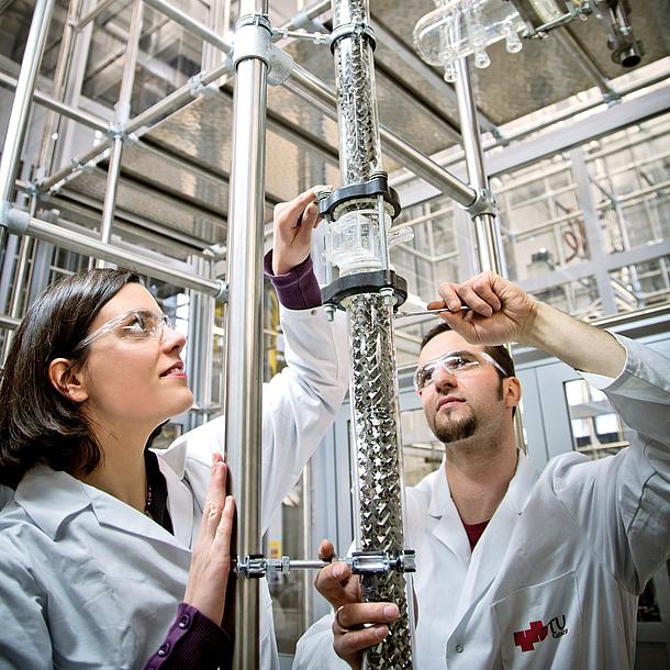 Eine Frau und ein Mann in Laborkleidung arbeiten an einem Rohr.