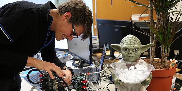 Ein Mann mit Brille beugt sich über ein Computergehäuse und arbeitet daran. Daneben steht eine grüne Figur von Yoda, die eine Schüssel mit Zetteln in der Hand hält.