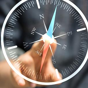 Eine Hand zeigt auf einen Kompass aus Glas. Bildquelle: vege – Fotolia.com
