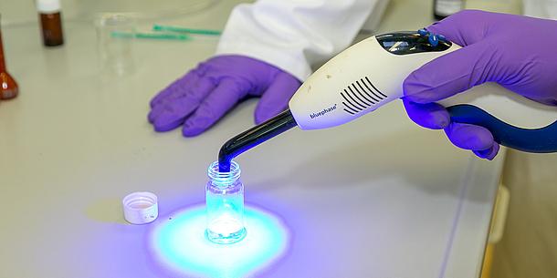 Nahaufnahme von Händen in Laborhandschuhen mit Lichtquelle.