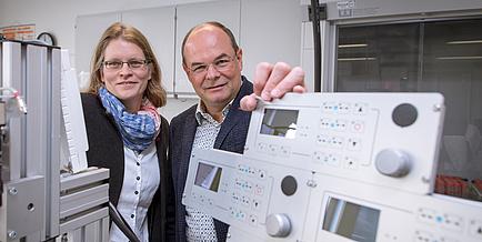 Eine Forscherin und ein Forscher stehen nehmen einem Laborgerät