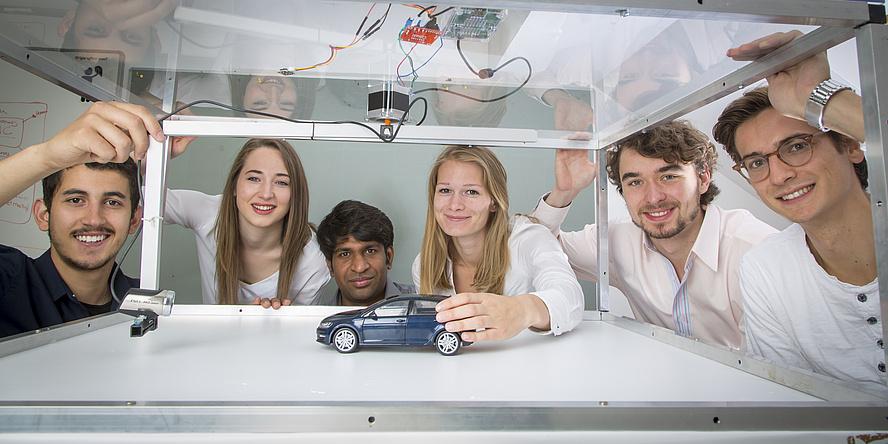 sechs junge Menschen betrachten ein kleines Spielzeugauto in einem Glaskasten