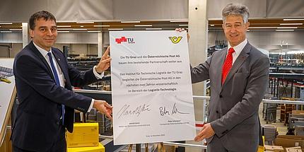 Zwei Männer in Anzügen halten ein gemeinsam unterschriebene Plakat in die Höhe