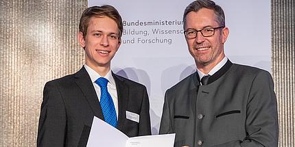 Elmar Pichl übergibt Ralph Stöckl eine Urkunde.