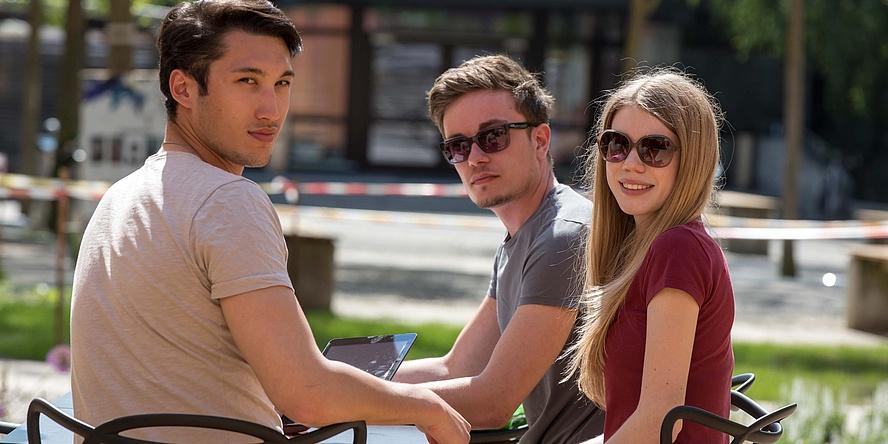 Zwei junge Männer und eine junge Frau im Gastgarten eines Cafés.