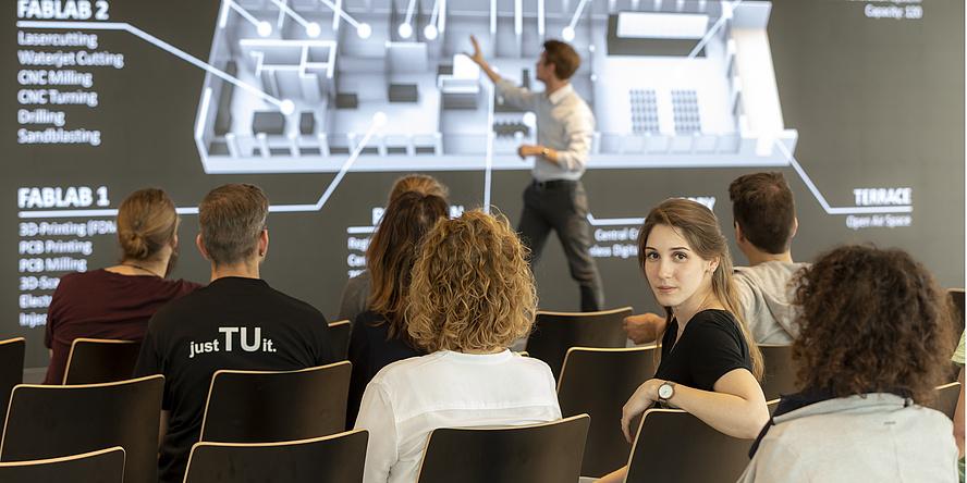 Frau im Publikum eines Vortrages blickt in die Kamera