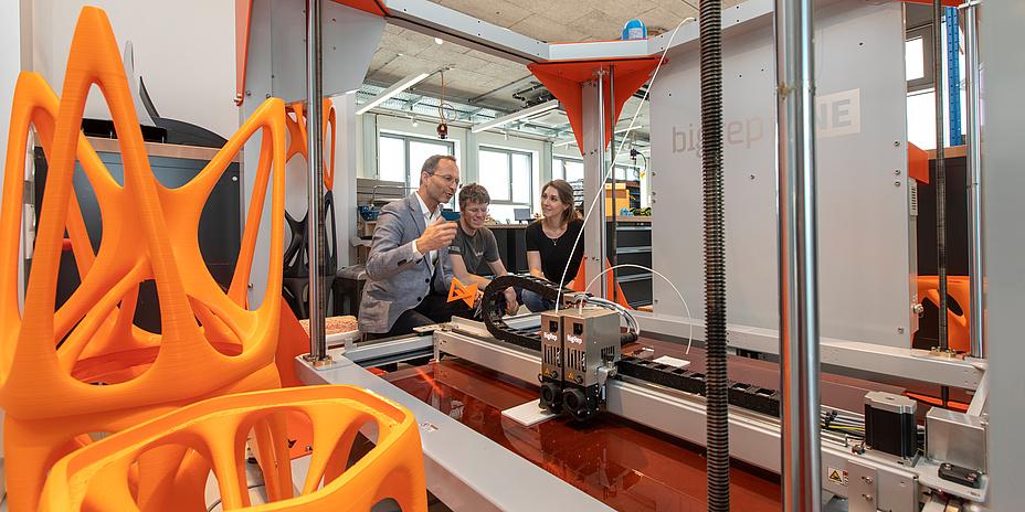 Produktionsmaschine mit futuristisch aussehenden orangen Hockern links im Vordergrund. Mittig hinten ein Mann mit Sakko und grau meliertem Haar, der einem jungen Mann und einer jungen Frau etwas erklärt.