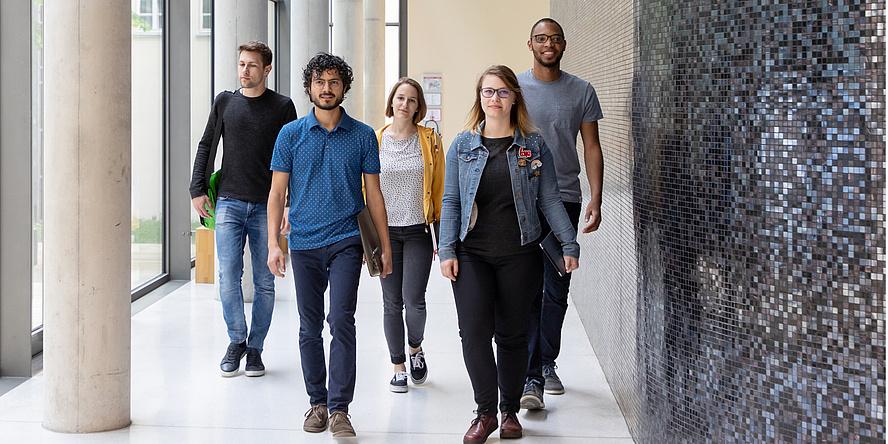 Drei Studenten und zwei Studentinnen gehen mit Schwung einen Gang entlang auf den Betrachter oder die Betrachterin des Fotos zu.
