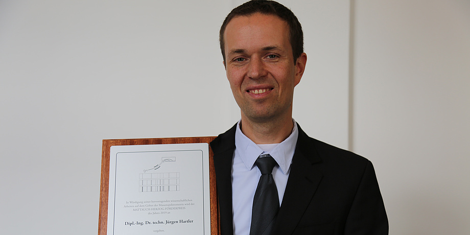 A man wearing a suit is smiling at the camera. He caries a certificate.