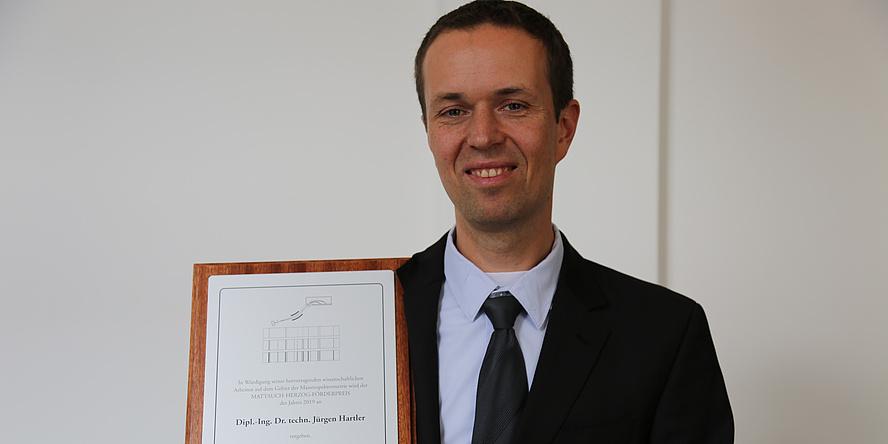 Ein Mann im Anzug lächelt in die Kamera. Er hält eine Tafel mit seiner Urkunde.