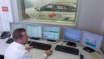 A gentleman in a white shirt watches five screens and in the background through a window a white car