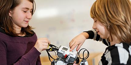 Ein Mädchen und ein Bub basteln an einem Fahrzeug aus Technik-Lego