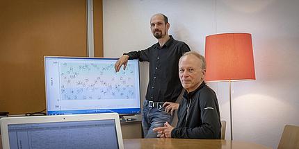 Ein Mann lehnt an einem Computerbildschirm. Ein anderer sitzt vor ihm auf einem Sessel.