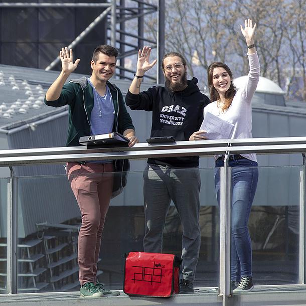Drei winkende Studierende.