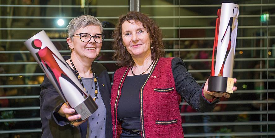 Zwei Frauen halten jeweils röhrenförmige, rot-silberne Trophäen hoch und lächeln in die Kamera.