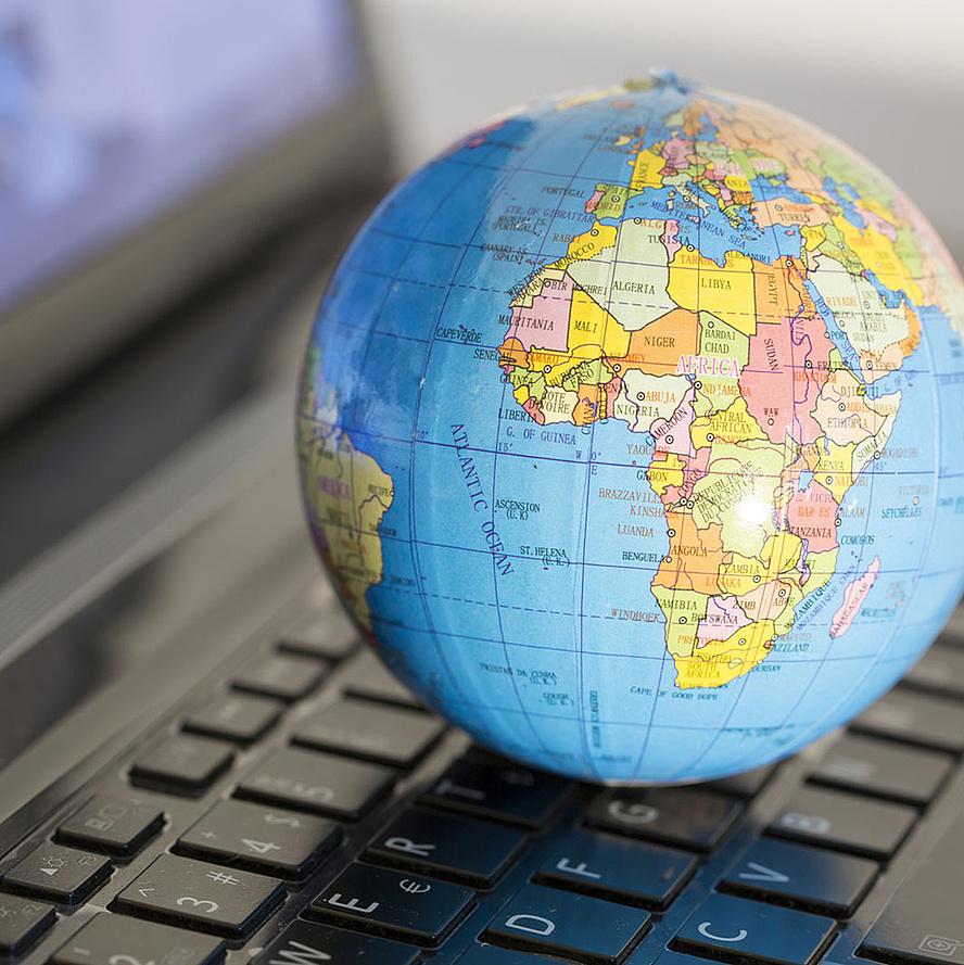Kleine Weltkugel, die auf einer Laptoptastatur liegt. Bildquelle: aytuncolym – Fotolia.com