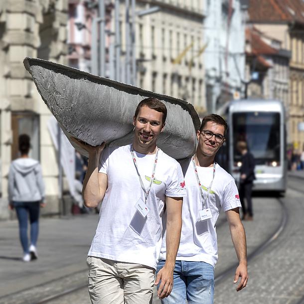 Zwei Männer tragen ein Betonkanu durch die Stadt.