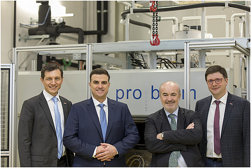 Four men stand smiling in front of a machine.