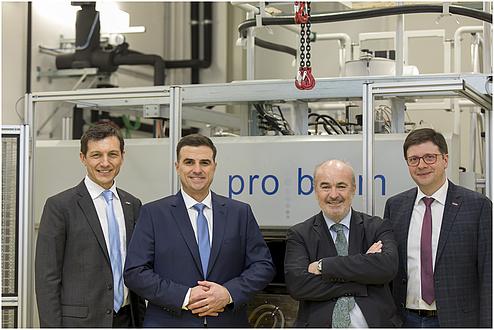 Vier Herren stehen lächelnd vor einer Maschine.
