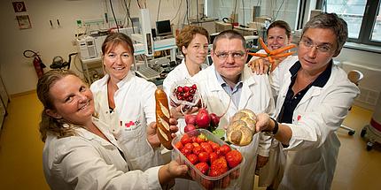 Sechs Personen im weißen Labormantel halten verschiedenste Nahrungsmittel in die Kamera.