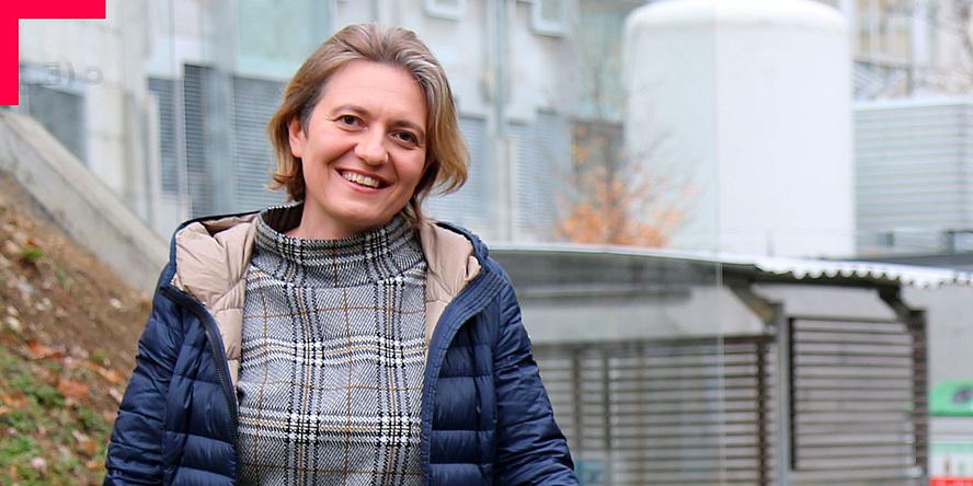 Frau im Halbporträt vor Forschungsgebäude