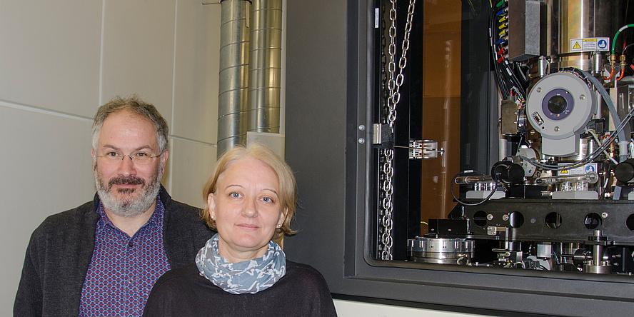 Forscher und Forscherin neben einem Elektronenmikroskop