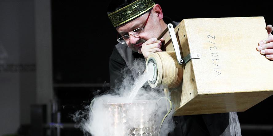 Ein Mann hält einen hölzernen Kanister und gießt eine rauchende Flüssigkeit aus.