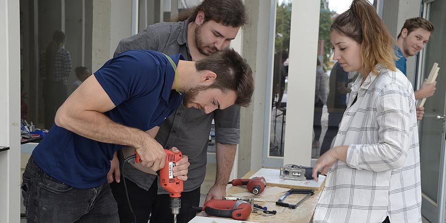 Zwei Studenten und eine Studentin stehen um einen Werktisch und bauen beim Ingenieurswettbewerb EBEC an der TU Graz mit Bohrmaschine und anderen Werkzeugen an einem Prototypen.