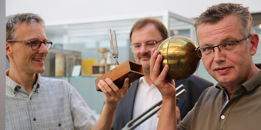 There are three men on the picture. Two of them are holding golden historic tuning forks. The third one on the right is looking at the camera and pointing a golden globe at his ear.