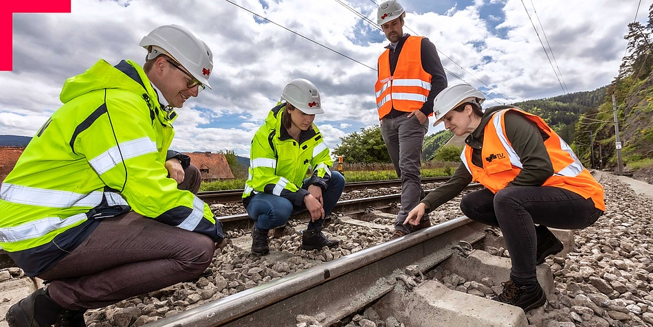 Two women and two men in high-visibility vests on a railroad track