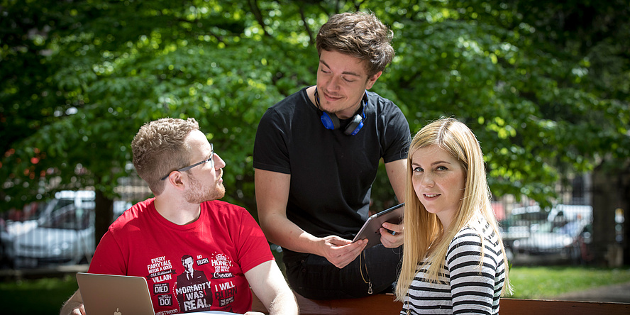 Drei junge Leute, ein Mann im roten T-Shirt daneben ein Mann im schwarzen T-Shirt und eine junge Frau mit blonden Haaren sitzen in der Natur und tauschen sich aus.