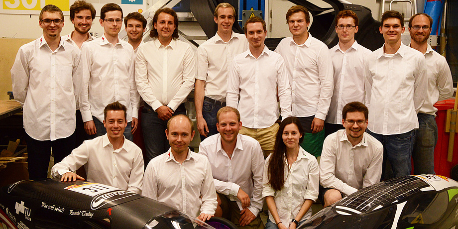 Members of the TERA TU Graz team – 15 guys and one woman, in white shirts, pose for the photo in two rows, in the foreground left and right two electric vehicles are partially in the picture.