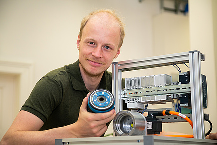 TU Graz researcher with small test bench and gearbox