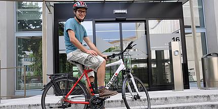 Ein Mann sitzt auf einem Fahrrad, das mit dem TU Graz-Logo versehen ist.