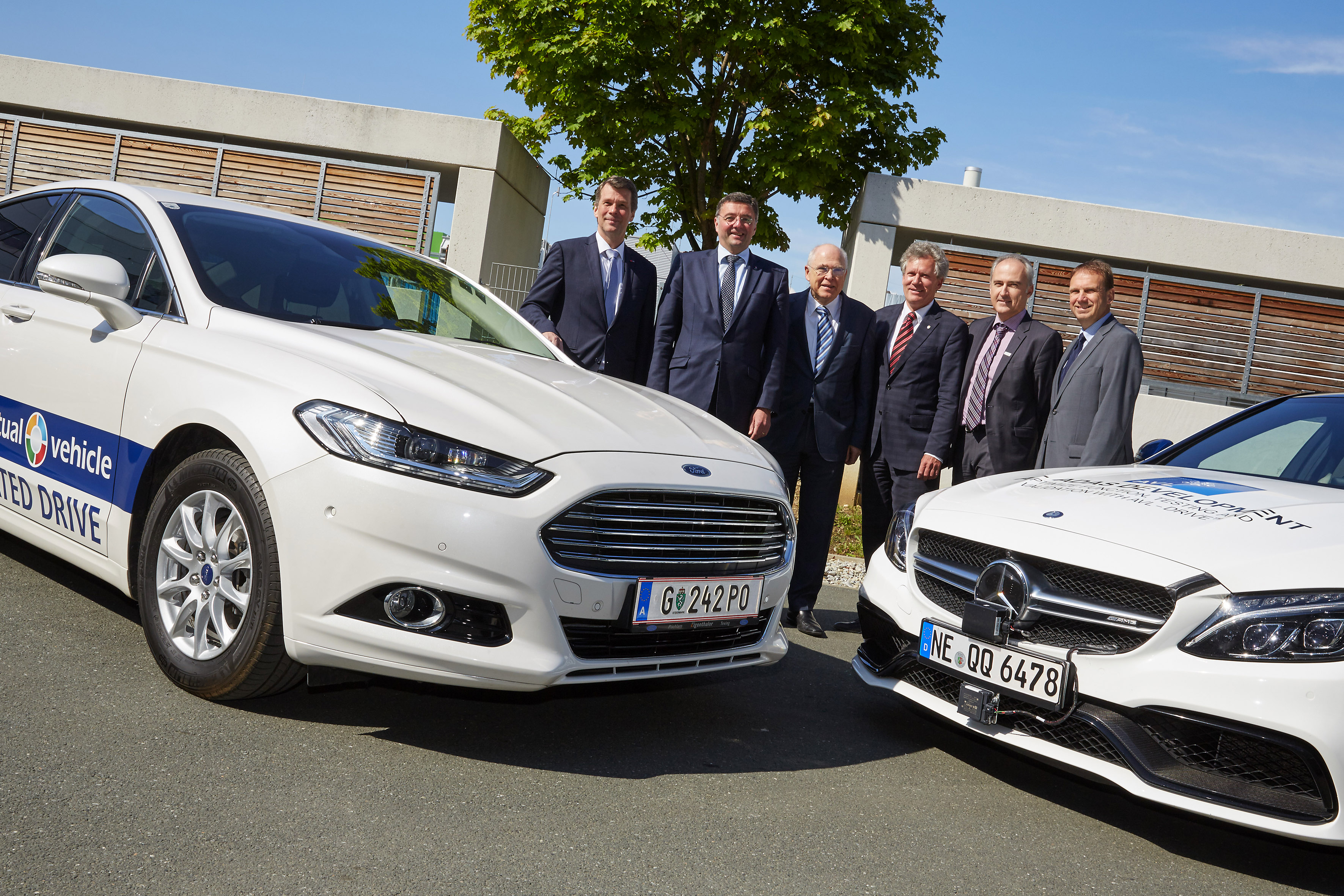 sechs Männer posieren neben zwei selbstfahrenden Autos