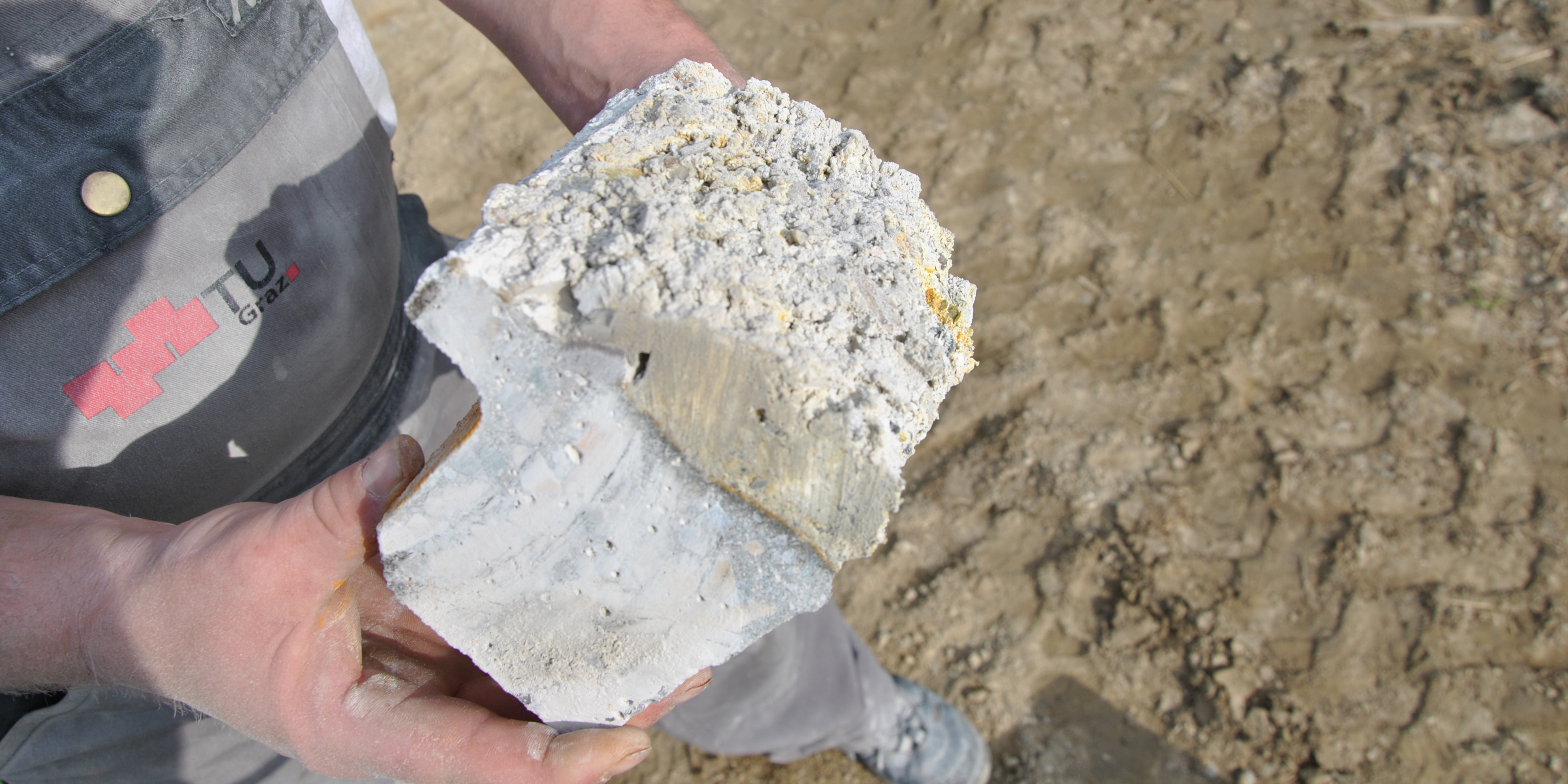 A male hand holds a concrete part damaged by microbial induced concrete corrosion (MICC); a centimetre-thick deposit has formed on the part.