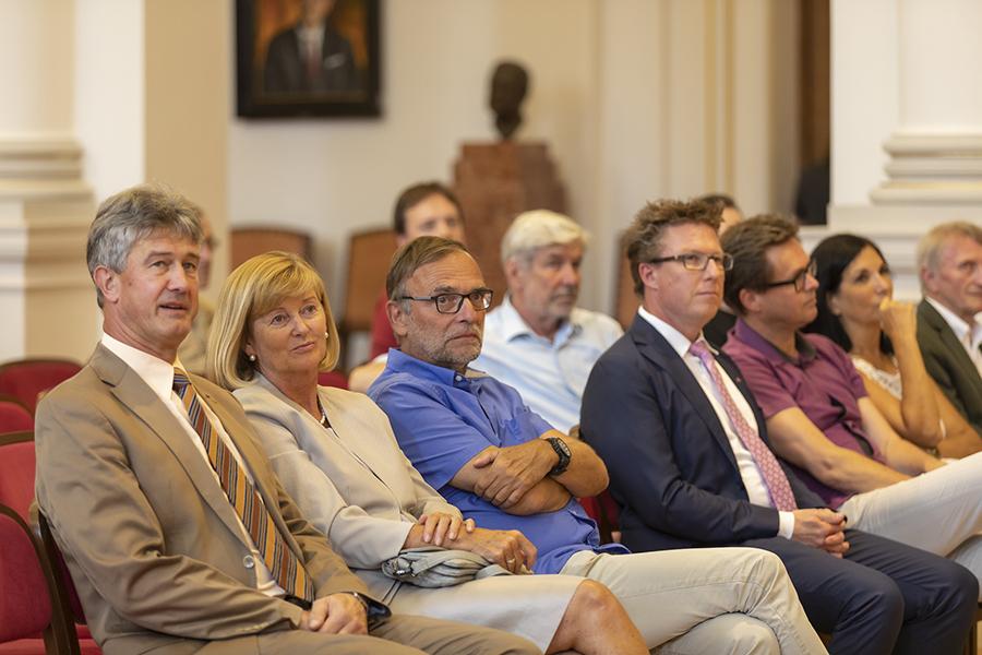 Eine Kinobestuhlung, sechs sitzende Personen hören sich einen Vortrag an