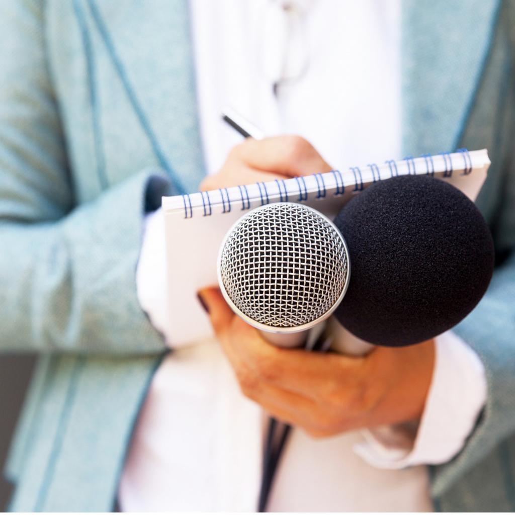 Hände mit Mikrofonen und Schreibutensilien
