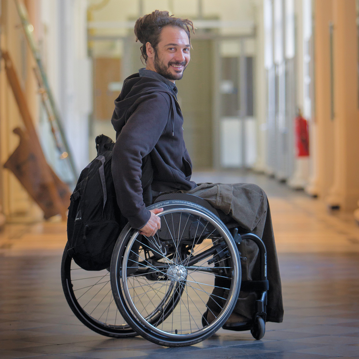 A man sits in a hallway of the TU Graz in a wheelchair. He is smiling at the camera.