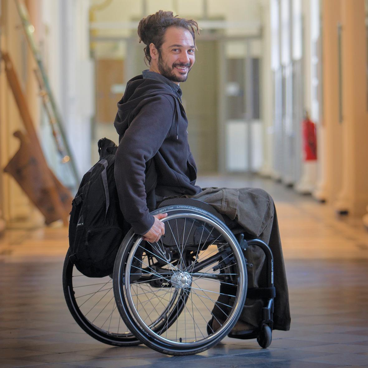 Ein Mann sitzt in einem Flur der TU Graz in einem Rollstuhl. Er lächelt in die Kamera.