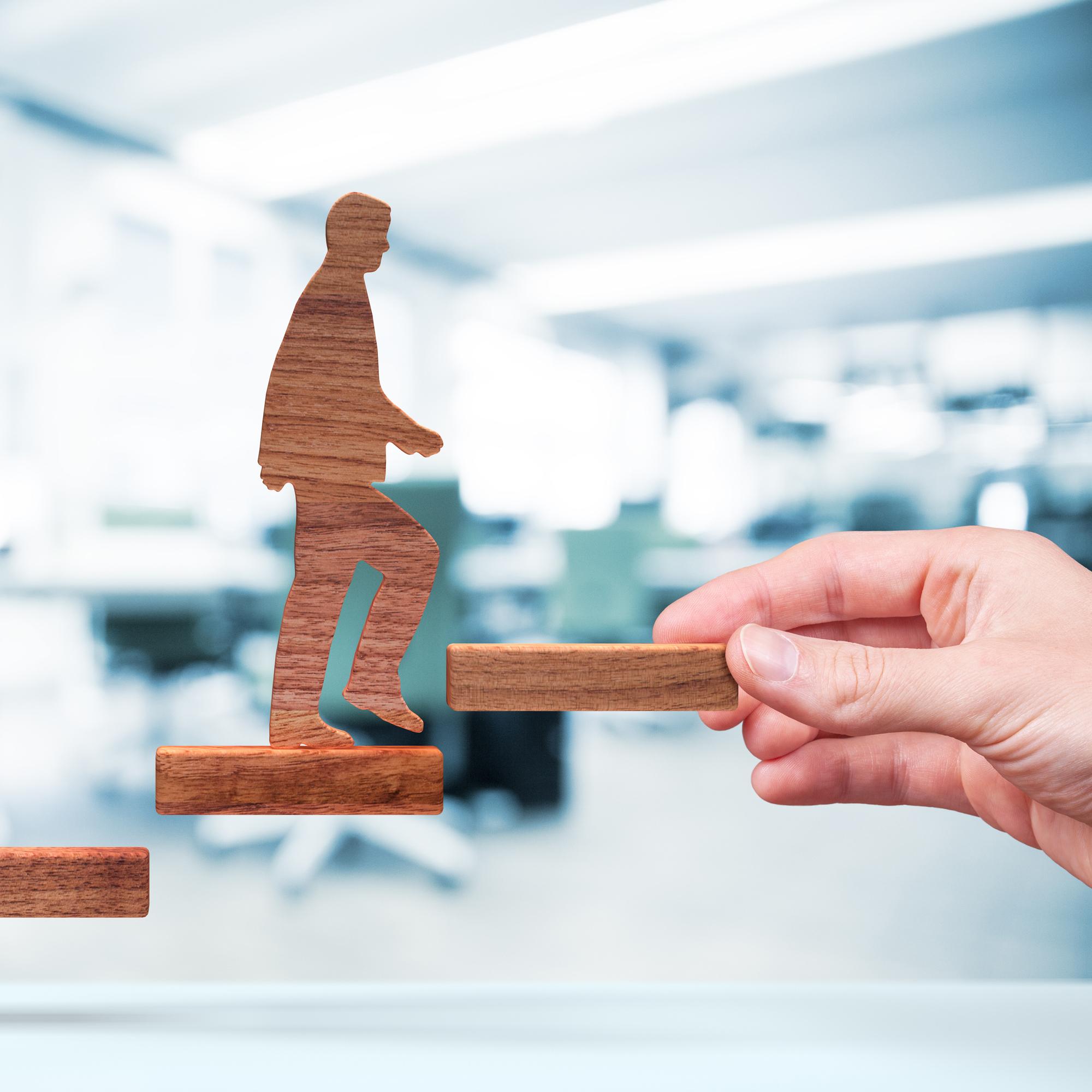 Eine Hand hält eine flache Holzstufe, die das Ende einer Stiege darstellt. Eine Holzfigur steigt die Stufen hinauf. Im Hintergrund ist ein Büro zu sehen.