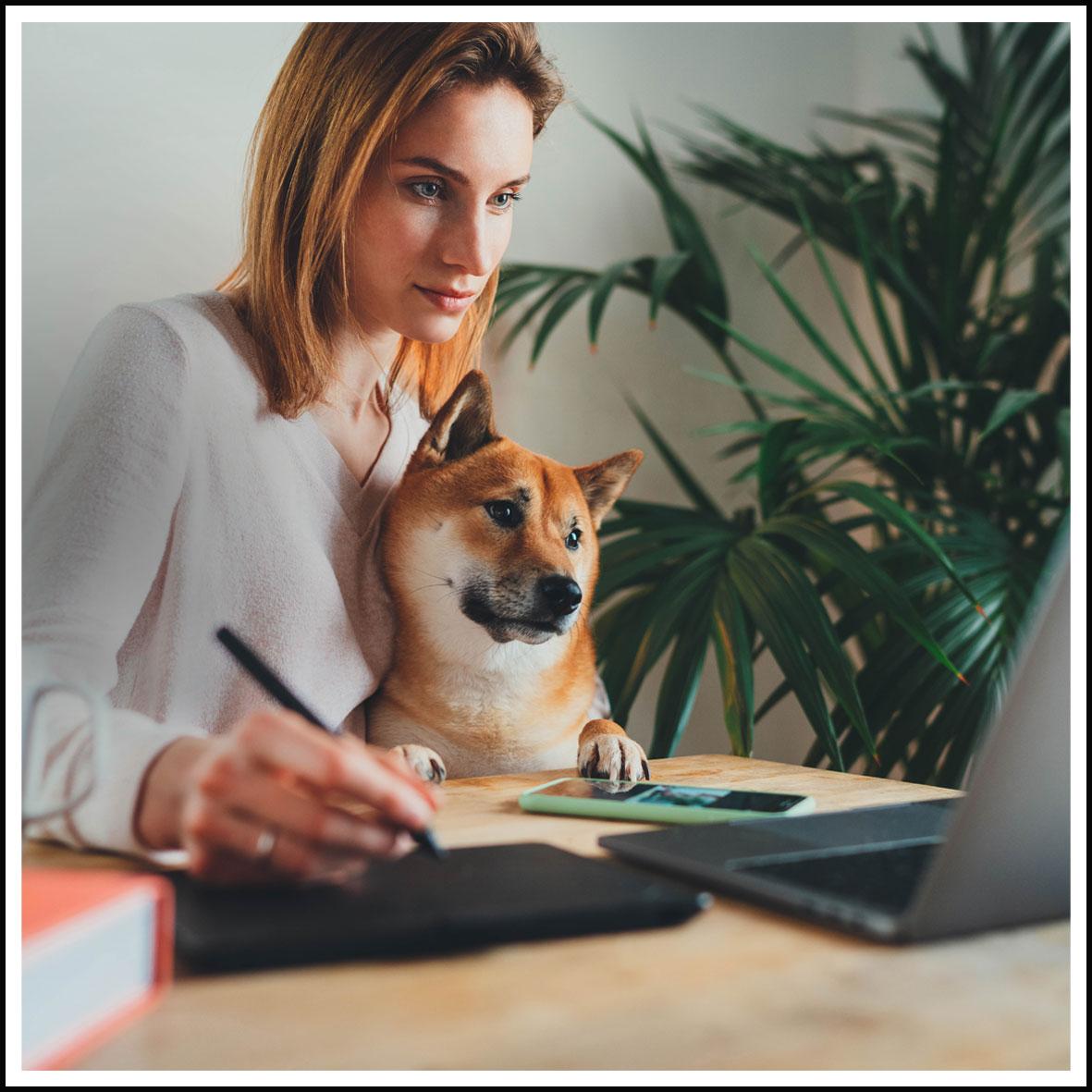 Eine Frau sitzt mit einem Hund an einem Tisch. Vor ihr steht ein aufgeklappter Laptop.