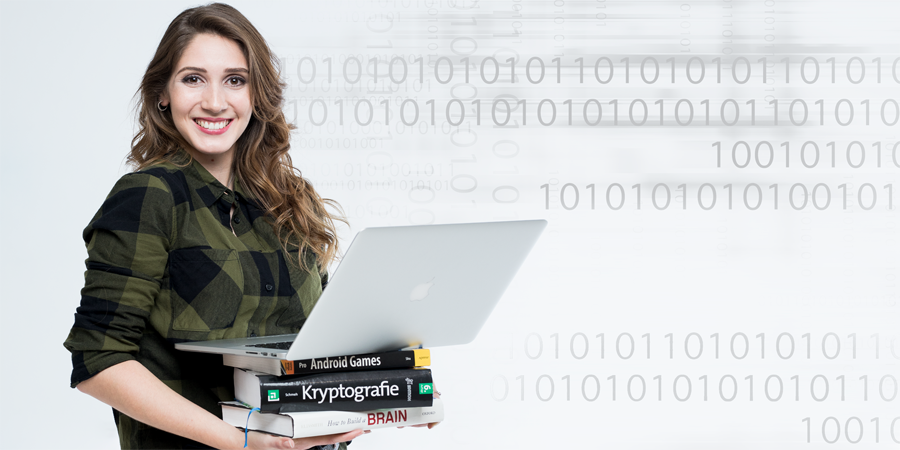Young woman holds a stack of books with an open laptop on top.